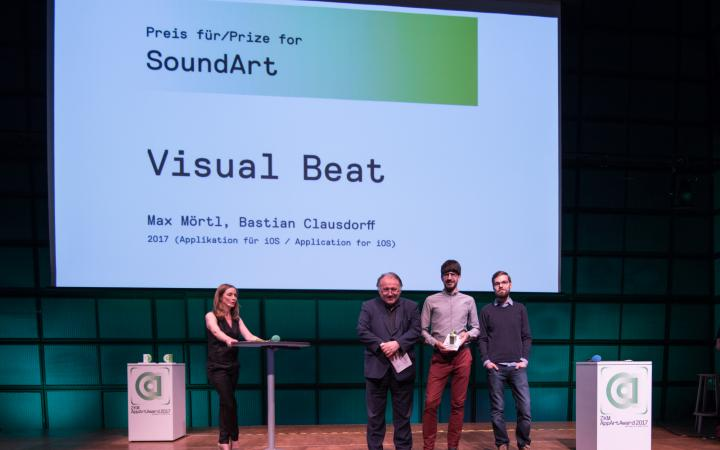 Drei Männer und eine Moderatorin auf der Bühne
