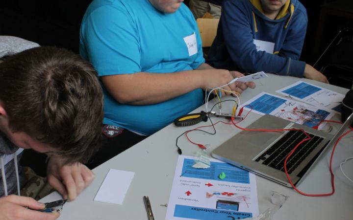 Ein paar Jungen sitzten gemeinsam am Tisch und arbeiten an einem Laptop und dem Bau eines Controllers.