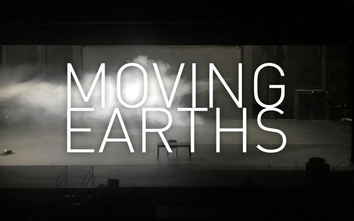 """An abandoned stage with a table and a chair, from the left fog is streaming through the picture and it is written large in the foreground: """"Moving Earths""""."""