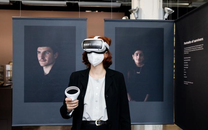 Zu sehen ist die Ko-Kuratorin Teresa Retzer, die mit VR-Brille im Ausstelungsraum steht