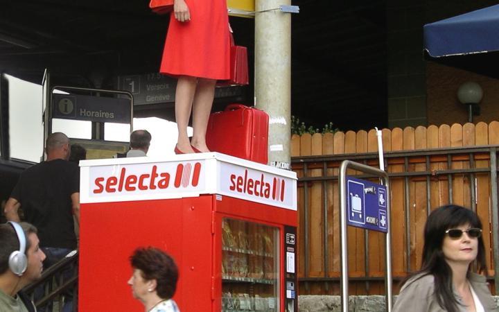Frau steht auf einem Süßigkeitenautomaten