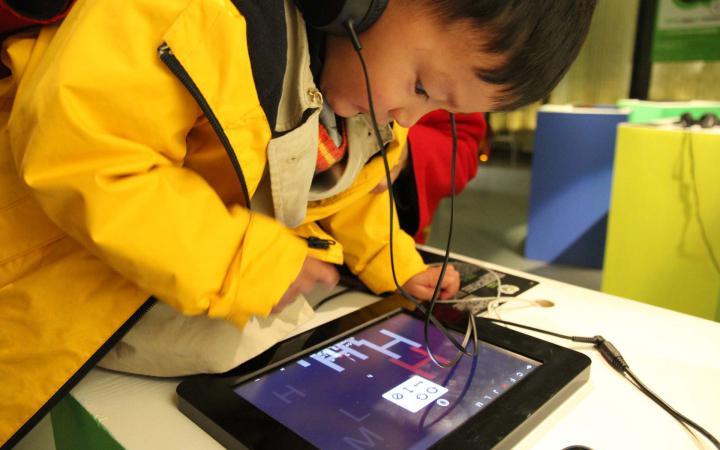 Ein kleiner chinesischer Junge ist über ein Ipad gebeugt.