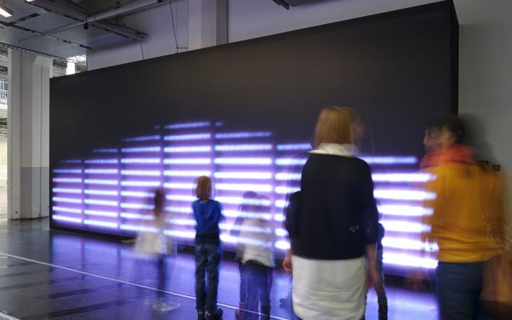 In einen Ausstellngsraum ist eine riesige Leinwand gestellt, die zu zwei Drittel ein leuchtendes, monochromes Raster zeigt. Davor stehen Menschen und betrachten die Installation.