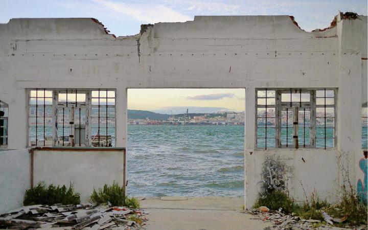 Das Bild zeigt eine Hausruine, durch deren offene Türen und Fenster man auf das Meer und eine dahinter liegende Stadt sehen kann.