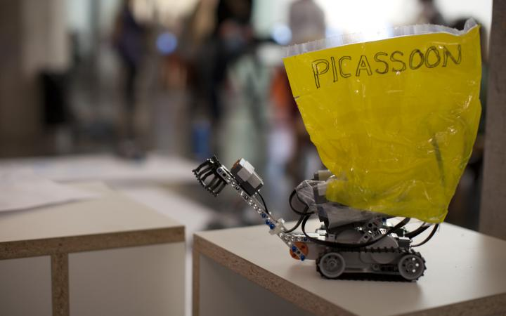"""On a table sits a little lego-robot on which a yellow paper is taped. It has the word """"picassoon"""" written on it."""