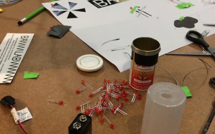 Auf einem Tisch liegen allerlei Utensilien zum werken, wie LEDs, Batterien, Werkzeuge und Papier verstreut herum. Darunter auch ein Blatt auf dem LEDs angebracht sind.