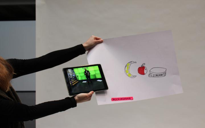 """Eine Frau hält ein Blatt vor sich auf dem eine Banane ein Apfel und ein Brot gezeichnet sind. Unten steht das Wort """"Alleskönner"""". Gleichzeitig hält sie noch ein iPad mit dem Foto eines Mannes vor einer grünen Wand in die Höhe."""