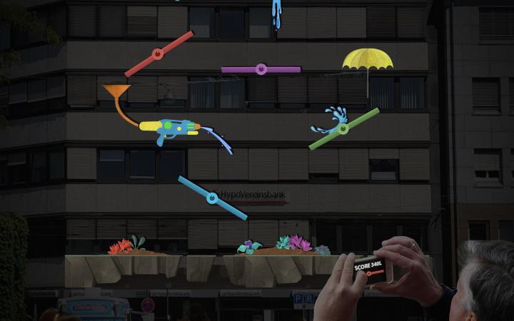 Eine riesige Projektion zeigt einzelne fabrige Elemente verteilt: ein langer Wasserhahn, eine Wasserpistole mit Trichter, ein Regenschirm.