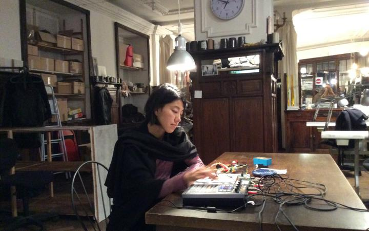 A young woman is sitting at a table in front of some technical devices. She's creating electronic music.