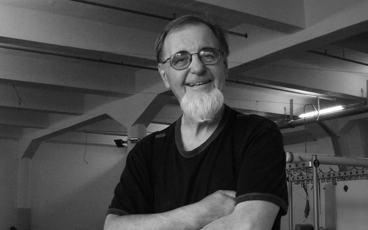 Portrait of Woody Vasulka in black and white: He stands, arms crossed, in his guest artist studio.