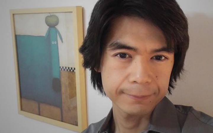 Takuto Fukuda holds his headset in his hand and looks into the camera.