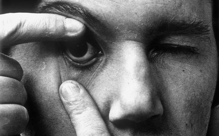 Die Portraitaufnahme zeigt Peter Weibel im Rahmen der Ausstellung »respektive Peter Weibel«. Auf dem Foto öffnet der Künstler sein rechtes Auge mit den Fingern.