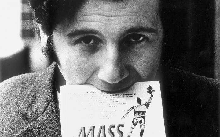 Die Portraitaufnahme zeigt Peter Weibel im Rahmen der Ausstellung »respektive Peter Weibel«. Auf dem Foto trägt der Künstler ein Buch mit seinem Mund.