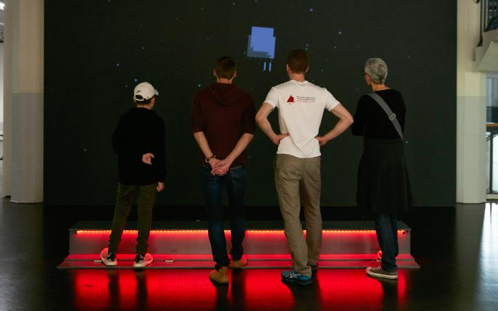 Four people stand before the installation of the computer game »Rakete«.