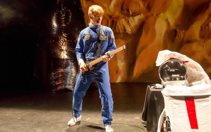 You can see a young man in a blue astronaut suit and a guitar in his hand.