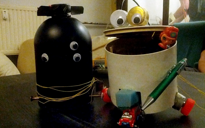Two little robots that are made out of junk are sitting next to each other, one is black and has 3 eyes and one is made out of a bin with 2 eyes out of bottle caps, that are placed on the open mouth resp. lid of the bucket.