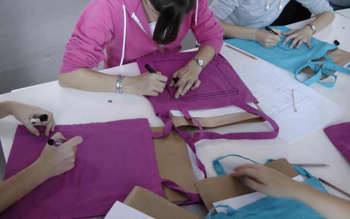 Mehrere Kinder bemalen ihre Taschen, die vor ihnen auf dem Tisch liegen, mit flotten Sprüchen.