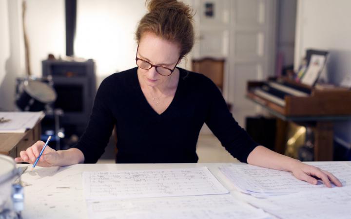 Foto einer Frau mit Brille und rötlichen Haaren, sie studiert ein Notenblatt, dass auf einem Tisch liegt.