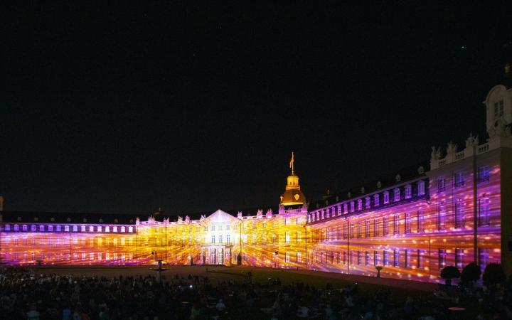 Die Fassade des Karlsruher Schlosses ist in bunten Farben angestrahlt. Es ist Nacht.