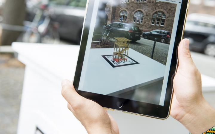 A tablet screen shows a virtual sculpture embedded in real space.