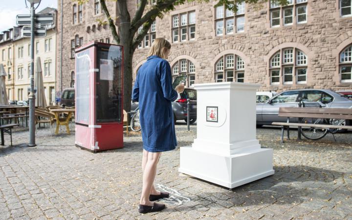 Eine Frau in blauem Kleid steht vor einem leeren weißen Sockel. Der Sockel gehört zum AR Kunstwerk »The People's Monuments«.