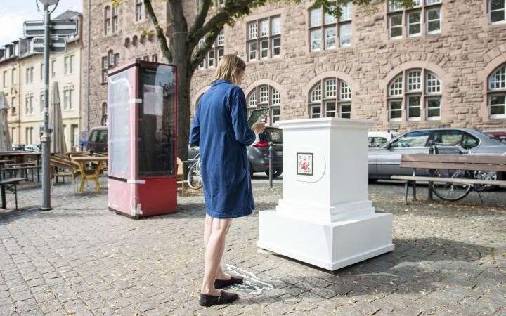 A woman in a blue dress stands in front of an empty white pedestal. The pedestal belongs to the AR artwork »The People's Monuments«.