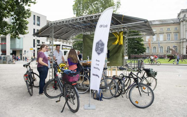 A group of people with bicycles in front of the Spacecraft_ZKM in Karlsruhe.