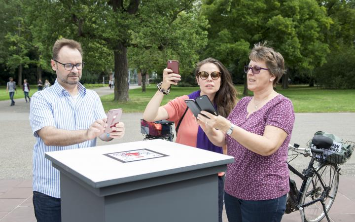 People with smartphones stand in front of an outdoor pedestal.