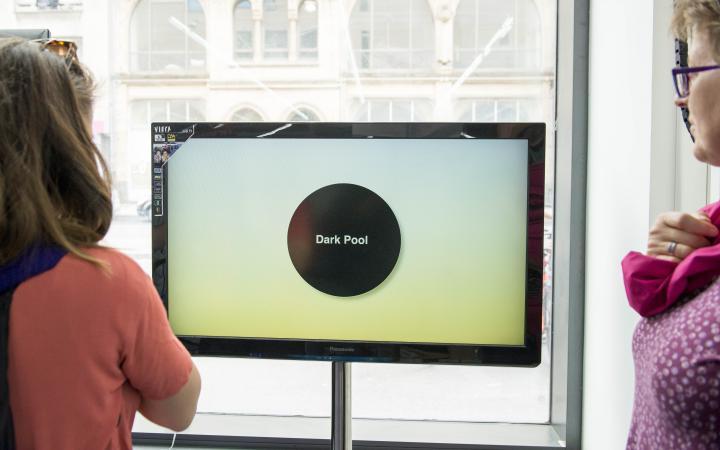 Das Foto zeigt zwei Frauen im Halbprofil, deren Gesichter nicht zu erkennen sind. Sie blicken auf eine nBildschirm auf dem ein schwarzer Kreis mit einer weißen Aufschrift Dark Pool« zu sehen ist.