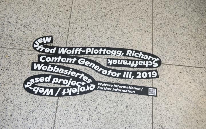 Auf einem gefließten Boden klebt die schwarze Schlaufe der Ausstellung »Seasons of Media Arts«, mit weißer Schrift über das Kunstwerk Content Generator III
