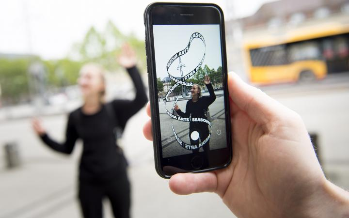 """In the foreground you can see a mobile phone with an app artwork on its display. The virtual """"Seasons of Media Arts"""" loop and a blonde woman trying to hold the ends of the loop together."""