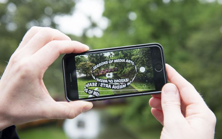Zwei Hände halten ein Iphone auf dem ein App-Kunstwerk geöffnet ist. Nun sieht man die kleine Brücke im Zoo über der die Ausstellungs-Schlaufe schwebt.