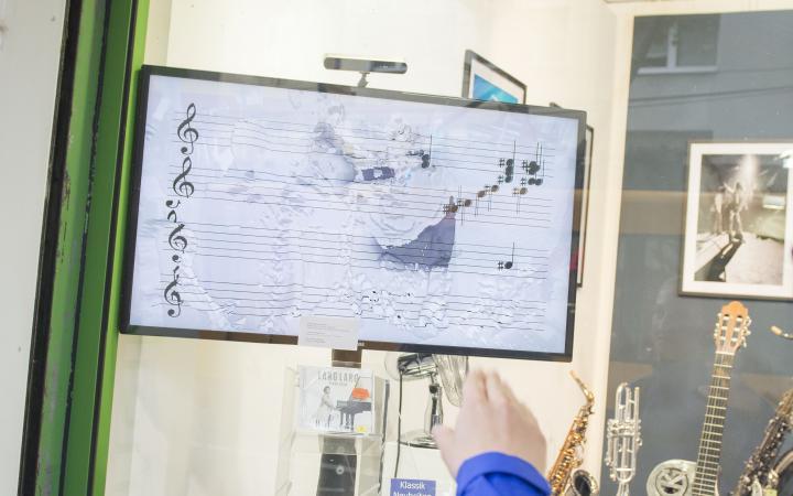In einem Musikschaufenster befindet sich ein Bildschirm auf dem PassantInnen interaktiv Sound produzieren können.