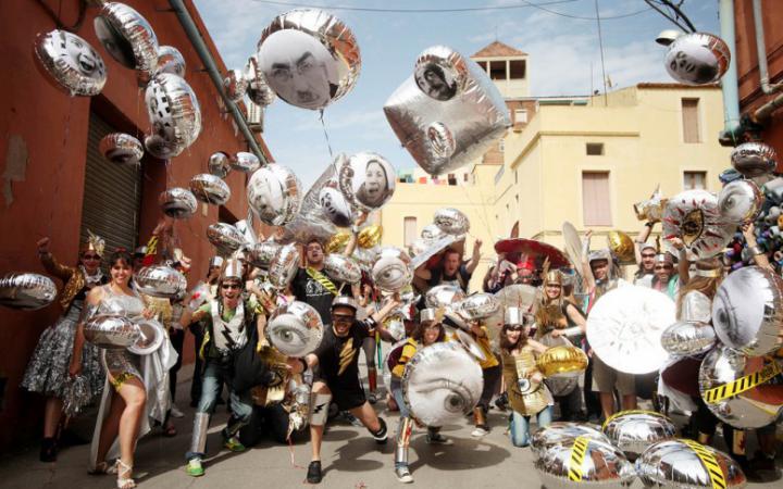 Eine ausgelassene Gruppe von Frauen und Männern steht auf der Straße und jeder hält einen silbernen Luftballon. Auf den Luftballons sind Bilder von Gesichtern und Augen. Die Menschen lachen und jubeln in die Kamera.