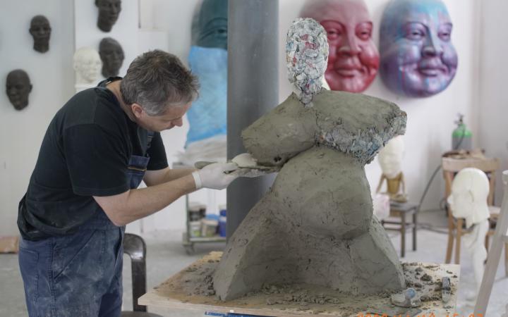 Ein Mann in Latzhosen modelliert eine voluminöse Figur aus Ton.