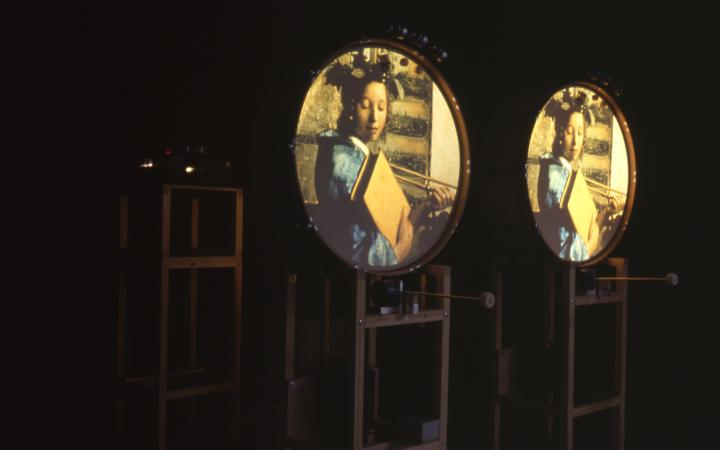 Zu sehen sind drei Gestelle. Auf zweien sind runde Flächen befestigt. Auf ihnen ist jeweils das gleiche Bild projiziert: eine junge Frau mit einem großen Buch in der Hand.