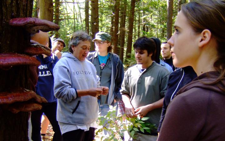 Lynn Margulis steht im Wald und erklärt einer Gruppe Studierender etwas.