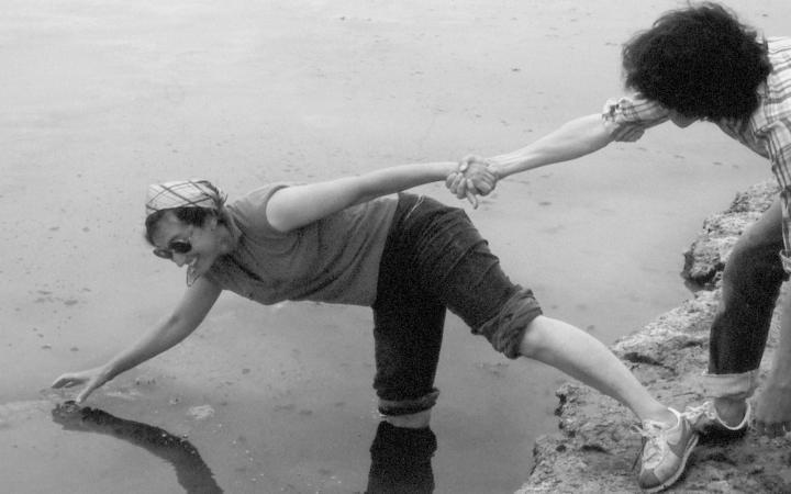 Lynn Margulis steht mit einem Bein im Wasser und hält den Finger einer Hand ins Wasser. Mit dem anderen Bein steht sie auf der Erde und die andere Hand hält eine fremde Hand fest. Sie steht gekippt und lacht.