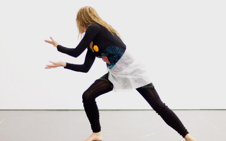 Eine junge Frau in schwarzer anliegender Kleidung ist in tänzerischer Pose abgebildet. Sie hat ihr Gewicht auf das rechte Bein verlagert, das sie angewinkelt hat. Das andere ist in einer Linie mit ihrem Oberkörper ausgestreckt.