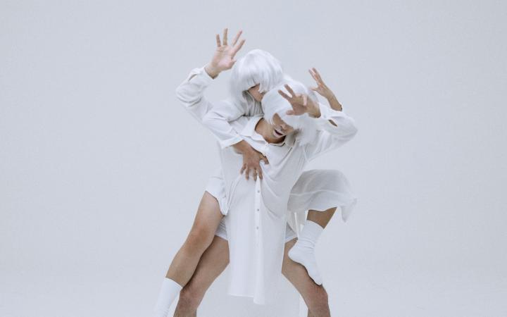 Zwei Tänzer. Sie haben beide silberne Perücken auf, ihre nackten Beine sind sichtbar, ihre Füße stecken in Strümpfen. Es wirkt abgespaced oder science-fiction-mäßig.