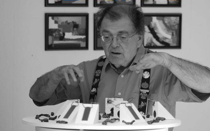 Mann steht mit gehobenen Händen vor Ausstellungsobjekt