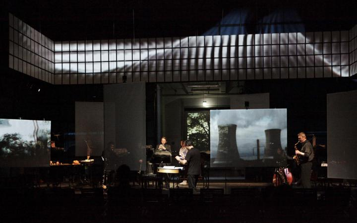 A music ensemble on a dusky stage. In the background a picture of a nuclear power station