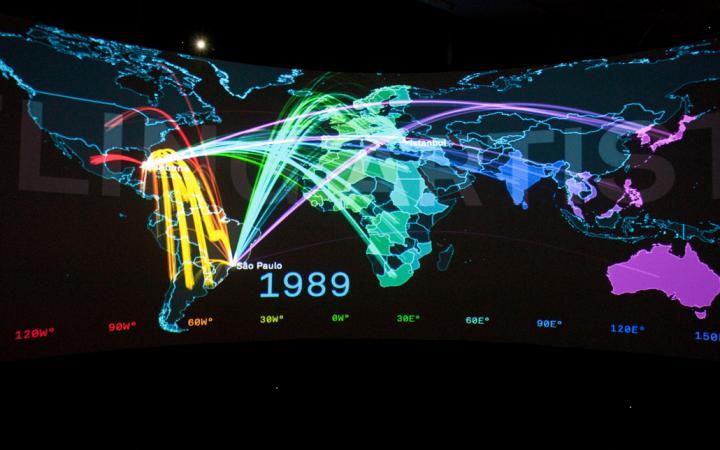 Eine sehr bunte Weltkarte mit ebenfalls bunten Verbindungslinien – datiert auf das Jahr 1989