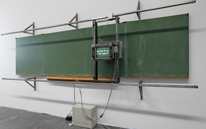 A monitor on rails in front of a blackboard