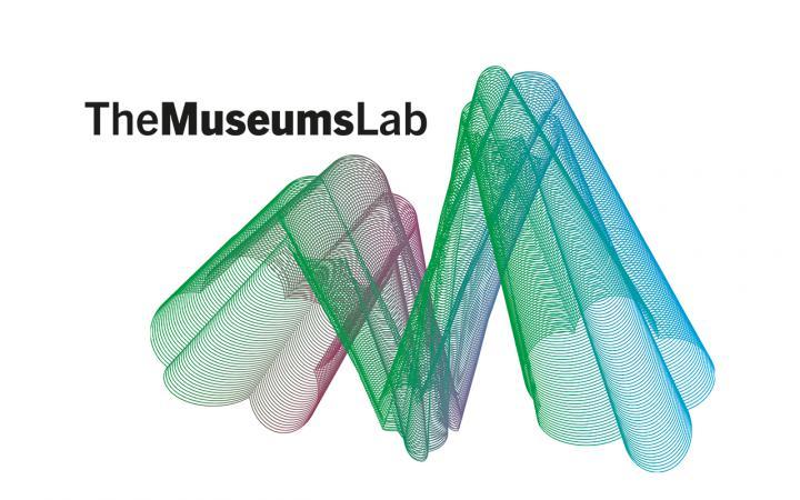 Ein grün-blaues geoemtrisches Konstrukt vor einem weißen Hintergrund. Links oben der Schriftzug »The MuseumsLab« in Schwarz.