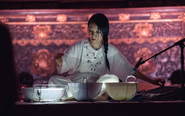 Foto der Komponistin Tomoko Sauvage vor Schalen, die mit Wasser gefüllt sind. In den Schalen hängen Mikrofone.