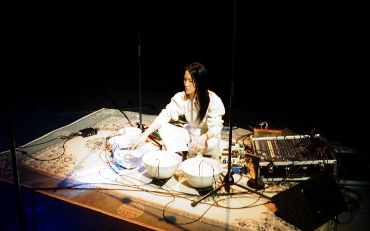 Tomoko Sauvage sitzt auf dem Boden, vor ihr stehen mit Wasser gefüllte Schalen und Mikrofone.