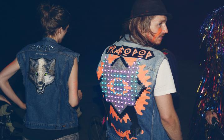 Ein Mann und eine Frau stehen mit dem Rücken zum Betrachter - ihre Jacken sind mit bunten LEDs bestückt