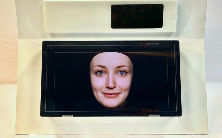 Ein kleiner Bildschirm zeigt ein Frauengesicht vor einem blauem Hintergrund.