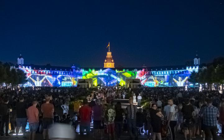 Impressionen aus Sportwettkämpfen wie der Olympiage zeigen sich in einer dynamischen Lichtershow auf der Fassader des Karlsruher Schlosses.